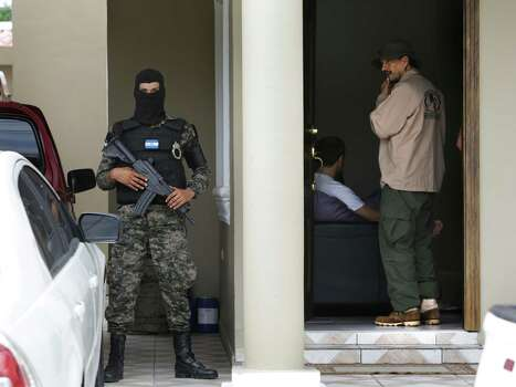 A SWAT team member of the Honduras Military Police stands guard in front of one of three luxury homes in the subdivision of El Pedregal in San Pedro Sula, as an investigator talks to a resident. The homes are owned by area drug and human trafficking groups, that are rented out to launder money. Thursday, June 26, 2014. Photo: Bob Owen, San Antonio Express-News / ©2013 San Antonio Express-News
