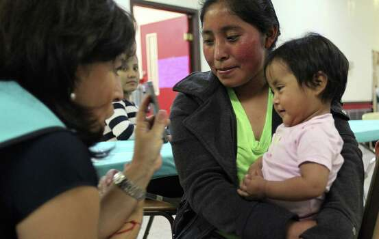 One-year-old Belinda Gomez and her mother, Maria Julia Gomez, 20, of Guatemala look at their photo taken by Catholic Charities volunteer Carmen Garza at the Sacred Heart shelter. / ©2014 San Antonio Express-News