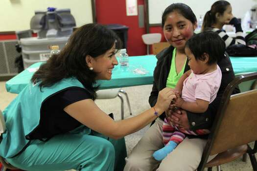 JUNE 26, 2014, 2:29 PM, MCALLEN, TEXAS - Catholic Charities volunteer Carmen Garza, left, plays with one-year-old Belinda Gomez, held by her mother, Maria Julia, 20, at the Sacred Heart shelter. The Guatemalans were headed to Atlanta. Photo: Jerry Lara, San Antonio Express-News / ©2014 San Antonio Express-News
