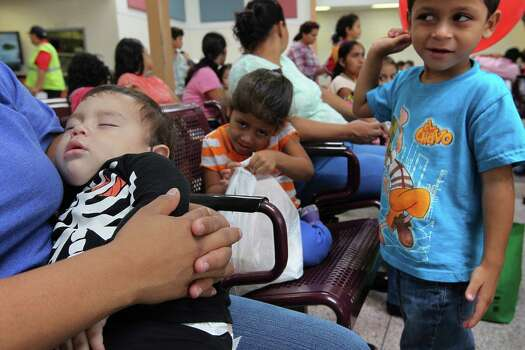 JUNE 26, 2014, 3:38 PM, MCALLEN, TEXAS - Five-year-old Oswaldo Ramirez looks at his mother, Olga Ramirez, 23, after being ordered to behave at the bus station. Traveling on a two-week journey from San Salvador, El Salvador, Ramirez also brought his sister, Marilyn, 4, center, and brother, Everson, 18 months. The family entered the country illegally and surrendered to Border Patrol agents. After their release from a detention center, they were headed to Maryland. Photo: Jerry Lara, San Antonio Express-News / ©2014 San Antonio Express-News