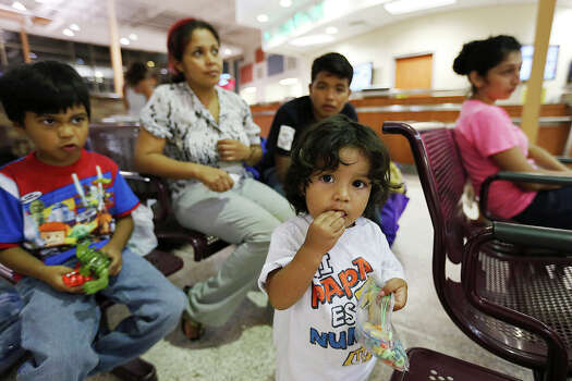 One-year-old Danny Hernandez, Jr. waits with family to board a bus for Long Island, New York at the terminal in McAllen, Texas, Wednesday, June 11, 2014. The family is from Zihualtepec, Honduras. With the child are from left, brother, Patrick, 6, mother, Jamileth Perez, 35 and brother, Leonel Alberto, 14. Relatives in the states purchased their tickets. A wave of Central American adults with children and unaccompanied minors has overwhelmed U.S. Immigration and Customs detention centers. Immigration officials release some of them on their own recognizance after undergoing processing. Photo: Jerry Lara, San Antonio Express-News / ©2014 San Antonio Express-News