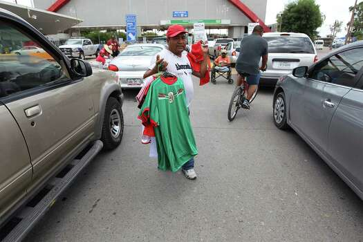 June 26, 2014, 1:41 p.m., Matamoros, Tamaulipas, Mexico - Vendor Andy (no last name given) sells Mexico soccer jerseys and Mexican flags to people waiting in their vehicles as they cross the international bridge to Brownsville. Photo: Kin Man Hui, San Antonio Express-News / ©2014 San Antonio Express-News