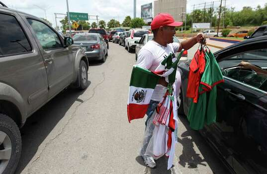 June 26, 2014, 1:41 p.m., Matamoros, Tamaulipas, Mexico - Vendor Andy (no last name given) offers to sell Mexico soccer jerseys and Mexican flags to drivers waiting in their vehicles as they cross the international bridge to Brownsville. Photo: Kin Man Hui, San Antonio Express-News / ©2014 San Antonio Express-News