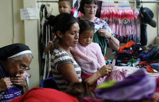 June 26, 2014, 4:39 p.m., Brownsville, Texas - Martina Santos Barrera Garcia (center) with her daughter, Lisbeth, pick out clothing at an immigrant welcoming center at Immaculate Conception Church run by Catholic Charities after she was released by Homeland Security. Garcia was released with a group of unauthorized immigrants at the bus station near the church and was walked over by Catholic Charities volunteers to the center to receive aid in the form of clothing, food and respite. According to paperwork for Garcia she was from the Republic of Honduras. Photo: Kin Man Hui, San Antonio Express-News / ©2014 San Antonio Express-News