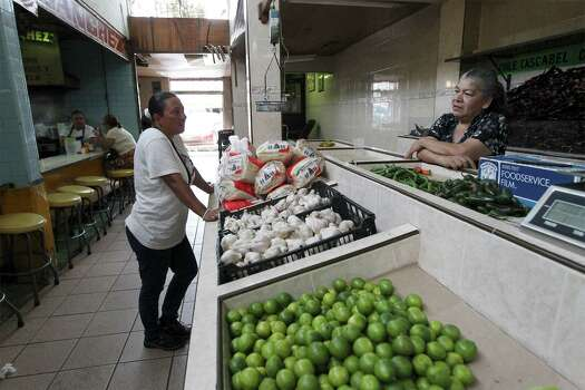 June 26, 2014, 12:14 p.m., Matamoros, Tamaulipas, Mexico - Brownsville resident Elizabeth Garcia (left) chats with shopkeeper Lourdes Sanchez at a market in Matamoros. Garcia often crosses the border into Mexico to shop and visit family. Photo: Kin Man Hui, San Antonio Express-News / ©2014 San Antonio Express-News