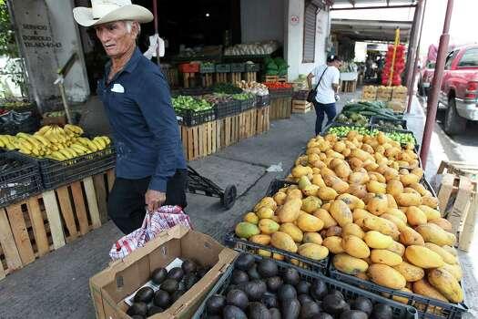 June 26, 2014, 12:17 p.m., Matamoros, Tamaulipas, Mexico - A man walks by stands of fruit in Matamoros. Photo: Kin Man Hui, San Antonio Express-News / ©2014 San Antonio Express-News
