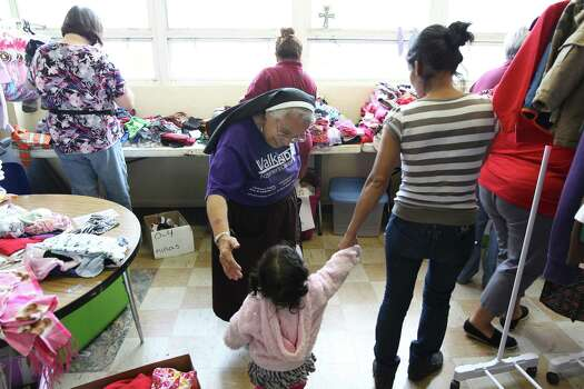 June 26, 2014, 4:46 p.m., Brownsville - Sister Evelyn Morales of Incarnate Word Academy in Brownsville reaches out to help a mother and her child at a welcoming center at Immaculate Conception Church. The center was opened to provide aid in the form of clothing, food and respite to the recent influx of immigrants crossing over the border. Photo: Kin Man Hui, San Antonio Express-News / ©2014 San Antonio Express-News