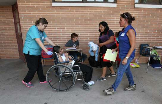 June 26, 2014, 5:18 p.m., Brownsville, Texas - Volunteers from Catholic Charities aid a young boy in a mud-caked wheelchair and his mother at the immigrant welcoming center at Immaculate Conception Church. Groups of unauthorized immigrants were released by Homeland Security at the bus station near the church and were escorted by Catholic Charities volunteers to the center to receive aid in the form of clothing, food and respite. Photo: Kin Man Hui, San Antonio Express-News / ©2014 San Antonio Express-News