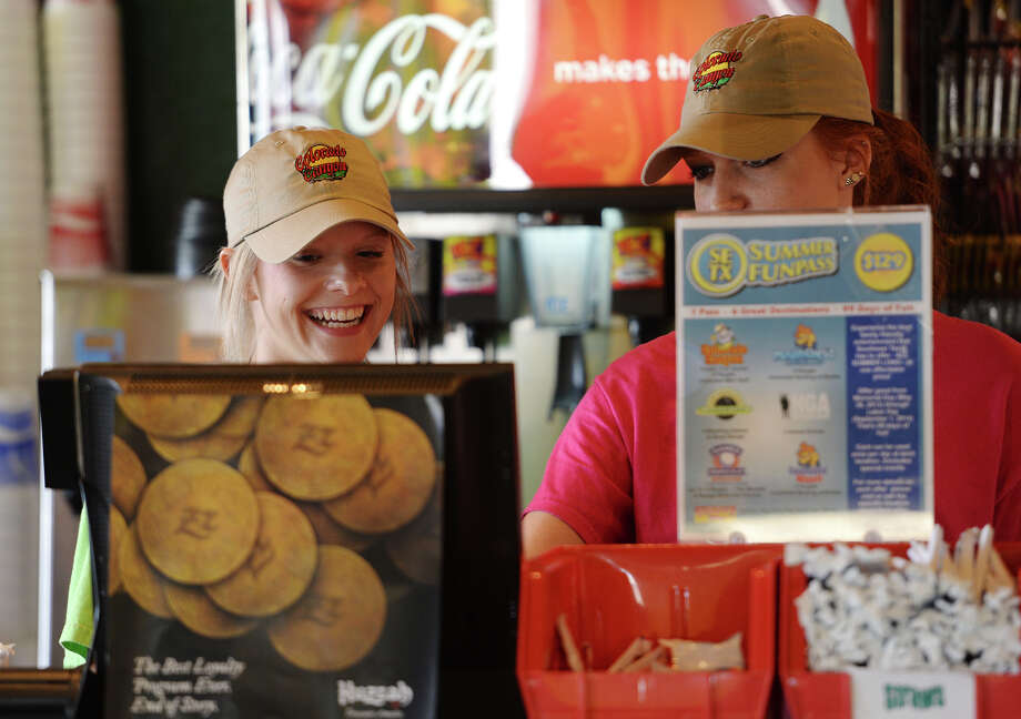 Hailey Tucker, left, smiles as she jokes with coworker Alicia Bright at the register of Colorado Canyon on Friday. Tucker has been working at Colorado Canyon since June. This summer was her first stint at the entertainment center, but it wasn't her first job. Photo taken Friday 8/8/14 Jake Daniels/@JakeD_in_SETX Photo: Jake Daniels / ©2014 The Beaumont Enterprise/Jake Daniels