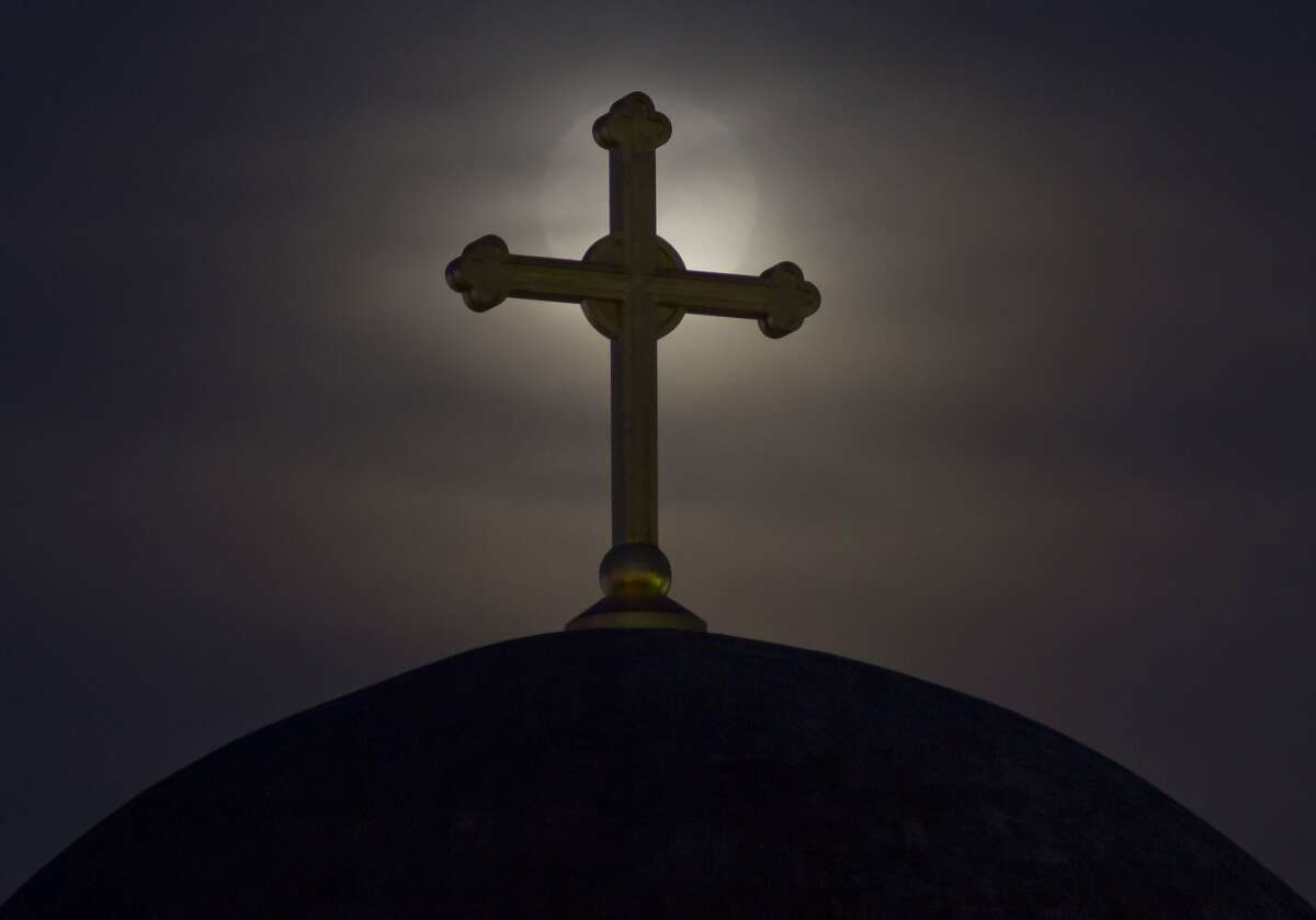 The moon appears behind a cross on the unfinished Serbian Orthodox church Christ the Saviour Cathedral, in Kosovo capital Pristina, Sunday, Aug. 10, 2014.