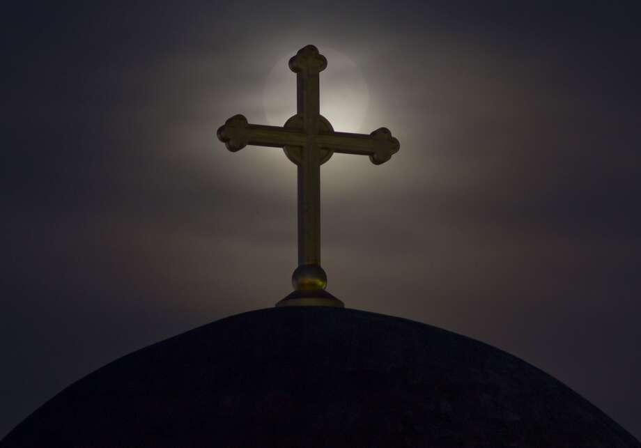 The moon appears behind a cross on the unfinished Serbian Orthodox church Christ the Saviour Cathedral, in Kosovo capital Pristina, Sunday, Aug. 10, 2014. Photo: Visar Kryeziu, Associated Press