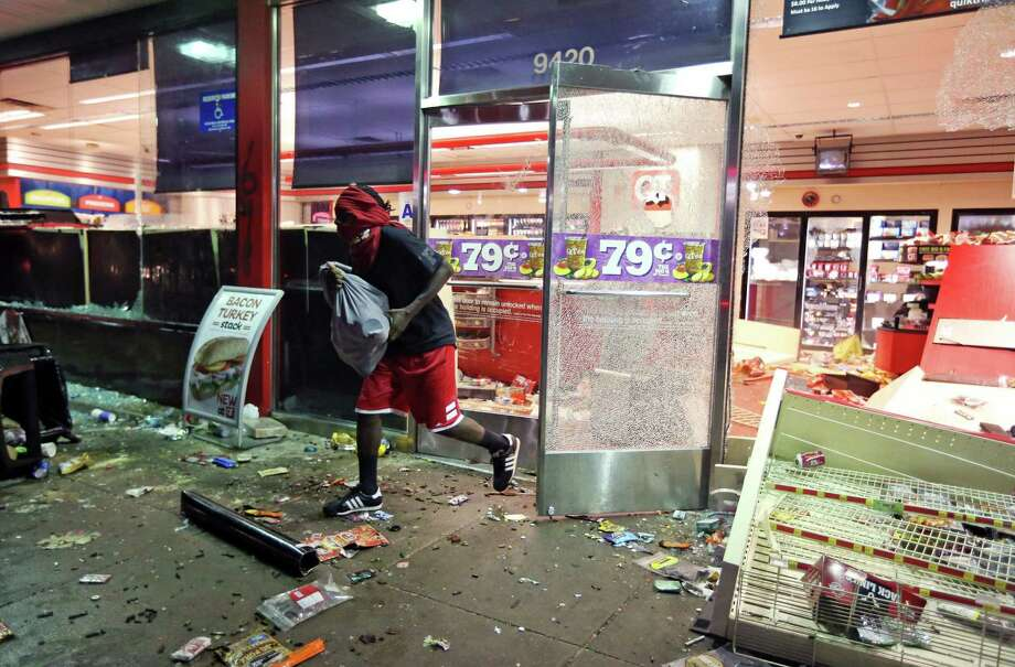 A man leaves a store on Sunday, Aug. 10, 2014, in Ferguson, Mo. A few thousand people crammed a suburban St. Louis street Sunday night at a vigil for unarmed 18-year-old Michael Brown who was shot and killed by a police officer, while afterward several car windows were smashed and stores were looted as people carried away armloads of goods as witnessed by an an Associated Press reporter. Photo: David Carson, AP / St. Louis Post-Dispatch