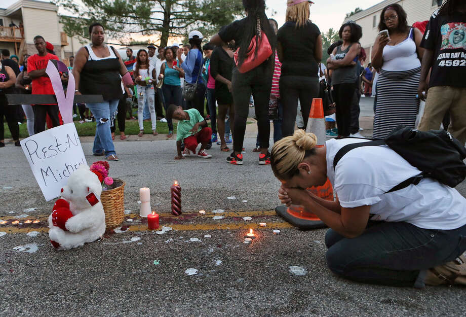 Meghan O'Donnell, 29, from St. Louis, prays at the spot where Michael Brown was killed, Sunday evening, Aug. 10, 2014, in Ferguson, Mo. A few thousand people have crammed the street where a black man was shot multiple times by a suburban St. Louis police officer. The candlelight vigil Sunday night was for 18-year-old Michael Brown, who died a day earlier. Police say he was unarmed. Photo: J.B. Forbes, AP / St. Louis Post-Dispatch