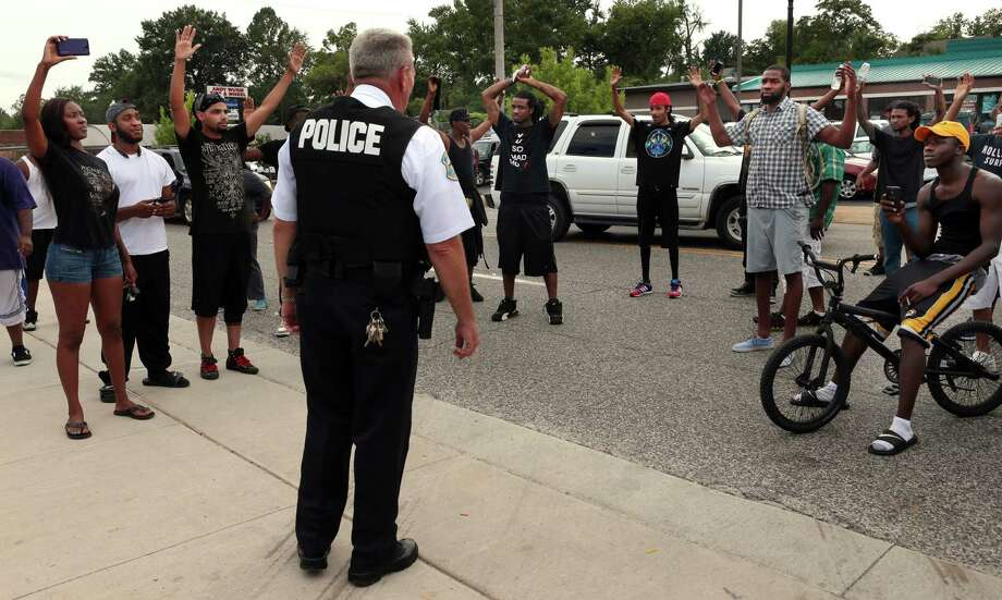 Protestors blocking Florissant Road raise their hands after being approached by police officers who asked them to stop blocking the street in front of the Ferguson police department on Sunday, Aug. 10, 2014, one day after a Ferguson officer shot and killed Michael Brown. Officers backed down and instead barricaded the street in both directions. Photo: Robert Cohen, AP / St. Louis Post-Dispatch
