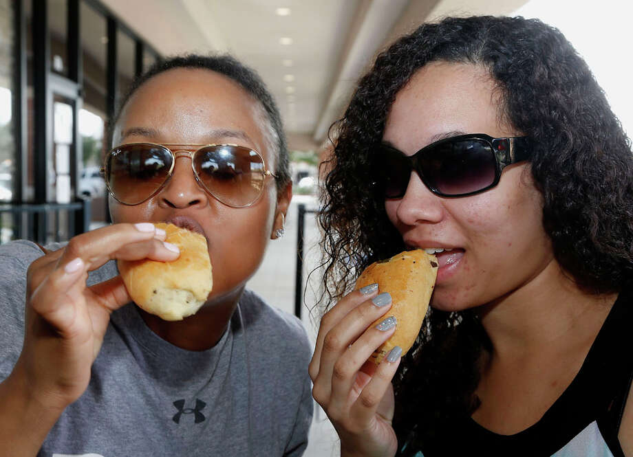 Teresa Harris left, and Emerald Kormah taste the Brisket Killache prepared with Killen's Barbecue brisket and Killen's coffee barbecue sauce while waiting in line at Pena's Donut Heaven and Grill. Photo: James Nielsen, Houston Chronicle / © 2014  Houston Chronicle