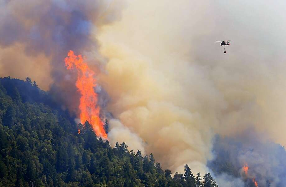 An Air National Guard helicopter moves in to make a water drop as the Lodge Fire Complex between Leggett and Laytonville, Calif., on  Friday Aug. 8, 2014.   Officials say eight firefighters who suffered burns while battling a wildfire in Northern California have been taken to the hospital. California Department of Forestry and Fire Protection Capt. Carlos Guerrero said Saturday that the injured firefighters are in stable condition after being airlifted to the burn center at the University of California, Davis for treatment. Officials say three firefighters from Santa Clara County and five inmate firefighters were burned fighting a blaze in Mendocino County late Friday night. (AP Photo, Kent Porter, Santa Rosa Press Democrat) Photo: Kent Porter, Associated Press