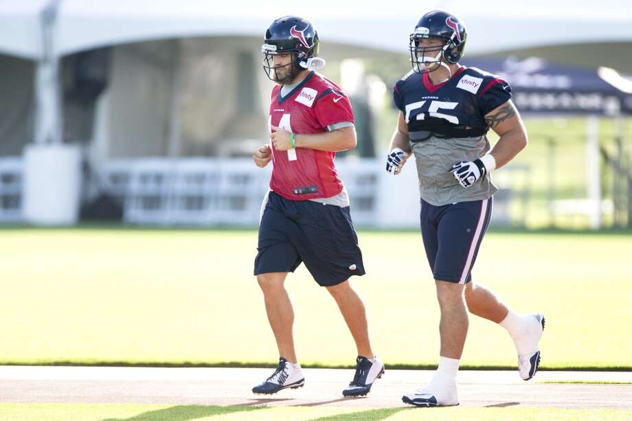Quarterback Ryan Fitzpatrick (14) and  center Chris Myers (55) jog onto the practice field. Photo: Brett Coomer, Houston Chronicle