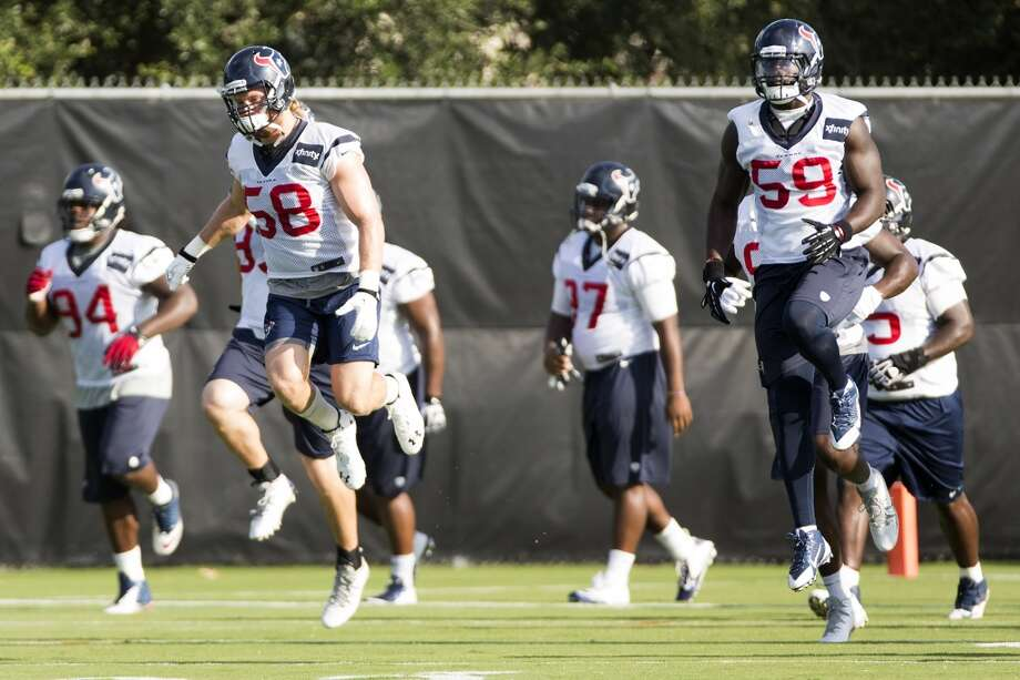 Outside linebackers Brooks Reed (58) and Whitney Mercilus (59) leap in the air while warming up. Photo: Brett Coomer, Houston Chronicle