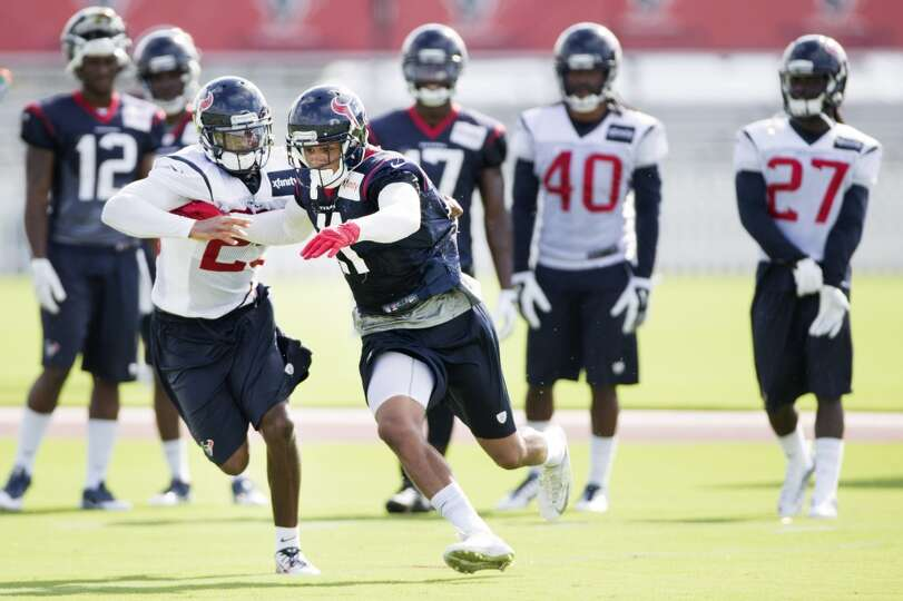 Cornerback Kareem Jackson (25) and wide receiver DeVier Posey (11) run a pass coverage drill.