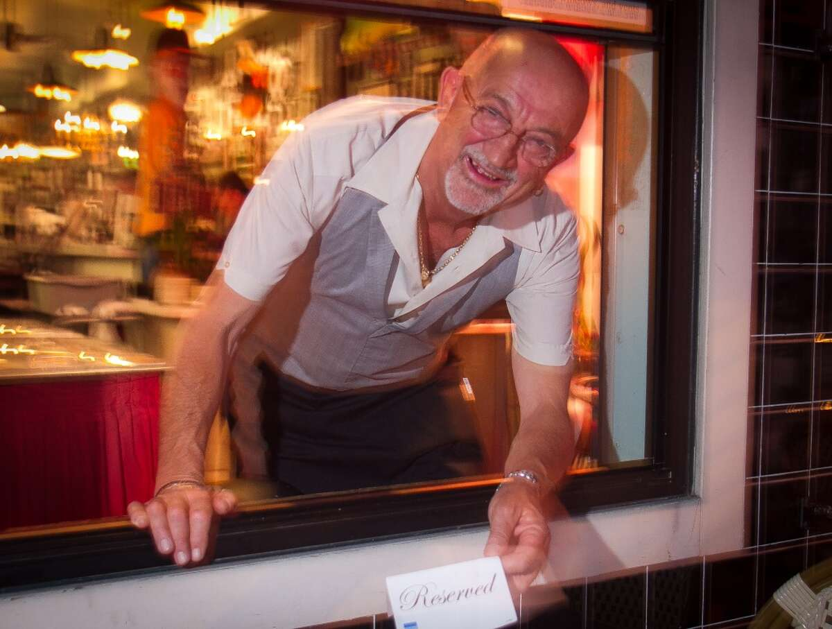 Gigi Fiorucci, owner Sotto Mare, puts a reserved sign on a table at his restaurant.