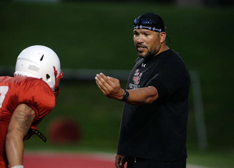 Eric Hicks directs Zach Johnson, No. 28, during drills at Wednesday night's practice. Hicks, linebac