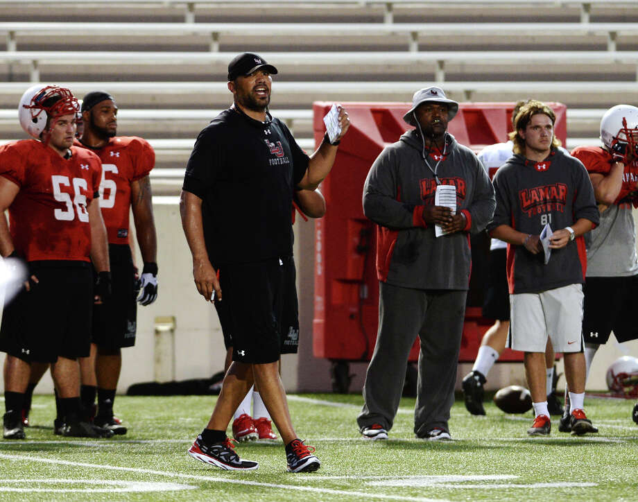 Eric Hicks watches the Lamar Cardinals run plays during Wednesday night's practice. Hicks, linebackers coach for the Lamar Cardinals, played for Maryland from 1994-1997 before leaving one year short of a degree to play in the NFL for 10 years. After his decade in professional football, he went back to school to earn his bachelor's degree in 2012.  Photo taken Wednesday 8/6/14 Jake Daniels/@JakeD_in_SETX Photo: Jake Daniels / ©2014 The Beaumont Enterprise/Jake Daniels