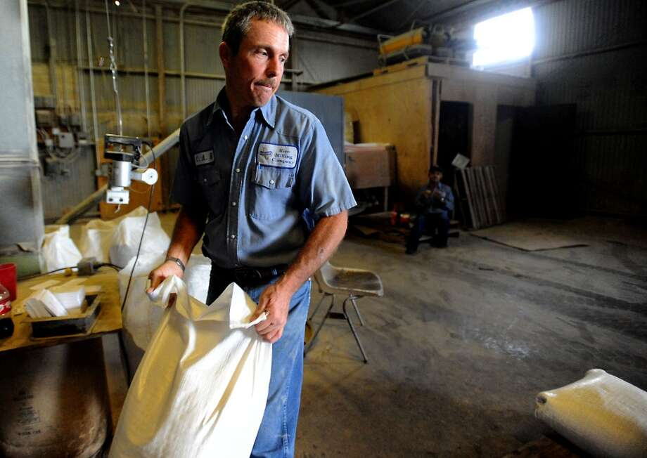 Carey Richardson moves a bag of rice to be shipped out at Doguet rice mill in Beaumont, Friday. Tammy McKinley, The Enterprise