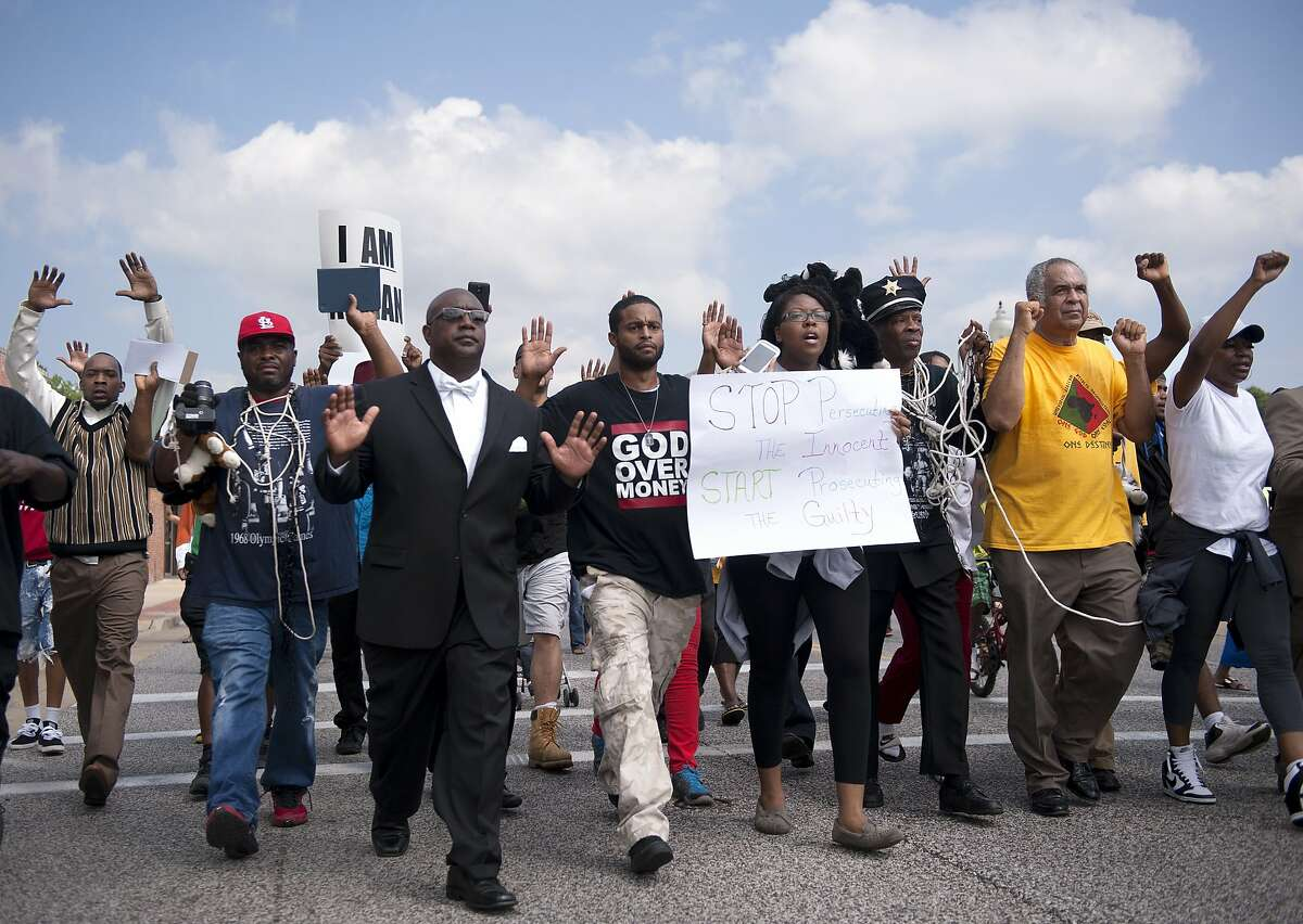 Protestors march along Florissant Road in downtown Ferguson, Mo. Monday, Aug. 11, 2014. The group marched along the closed street, rallying in front of the town's police headquarters to protest the shooting of 18-year-old Michael Brown by Ferguson police officers. Brown, who was killed in a confrontation with police in the St. Louis suburb, was shot Saturday, Aug. 9, 2014, and died following the confrontation with police. (AP Photo/Sid Hastings)