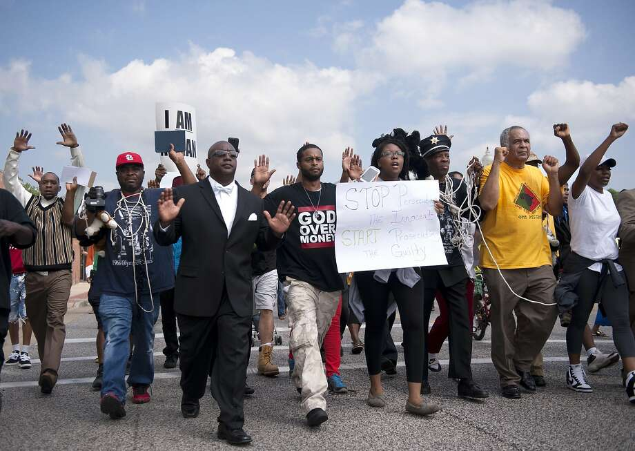Protestors march along Florissant Road in downtown Ferguson, Mo. Monday, Aug. 11, 2014. The group marched along the closed street, rallying in front of the town's police headquarters to protest the shooting of 18-year-old Michael Brown by Ferguson police officers. Brown, who was killed in a confrontation with police in the St. Louis suburb, was shot Saturday, Aug. 9, 2014, and died following the confrontation with police.  Photo: Sid Hastings, Associated Press