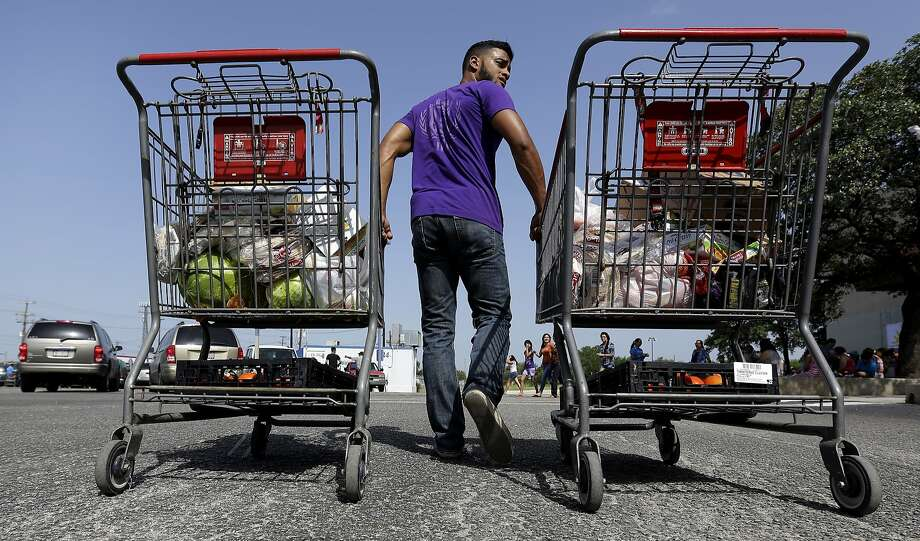 In this July 3, 2014 photo, a volunteer helps distribute groceries at a food bank at the Abundant Life Church in San Antonio. The food bank is cosponsored by the Libre Initiative, partly funded by conservative billionaires Charles and David Koch, which is looking to make inroads with the rising voting block of Hispanics. (AP Photo/Eric Gay) Photo: Eric Gay, Associated Press