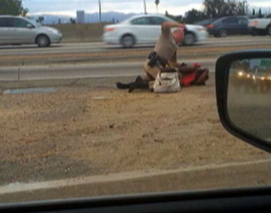 In an image taken from video provided by a motorist, a CHP officer straddles Marlene Pinnock while punching her in the head on the shoulder of a Los Angeles freeway on July 1. Photo: David Diaz, Associated Press