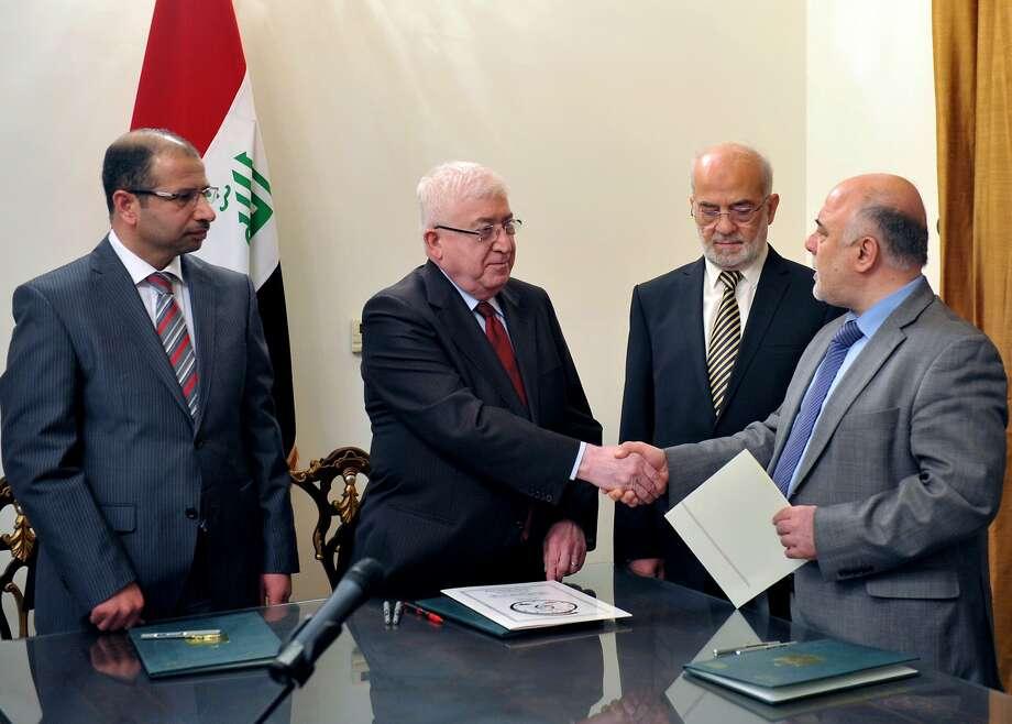Iraqi President Fuad Masum (center) congratulates Prime Minister-designate Haider al-Abadi. Photo: -, AFP/Getty Images