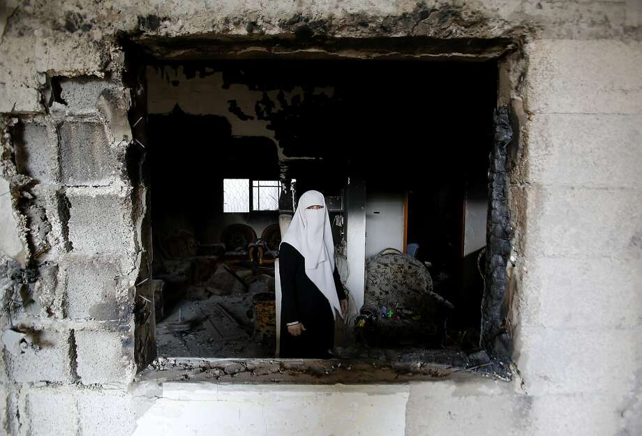 A Palestinian woman stands in her gutted home in Gaza City's Shijaiyah 