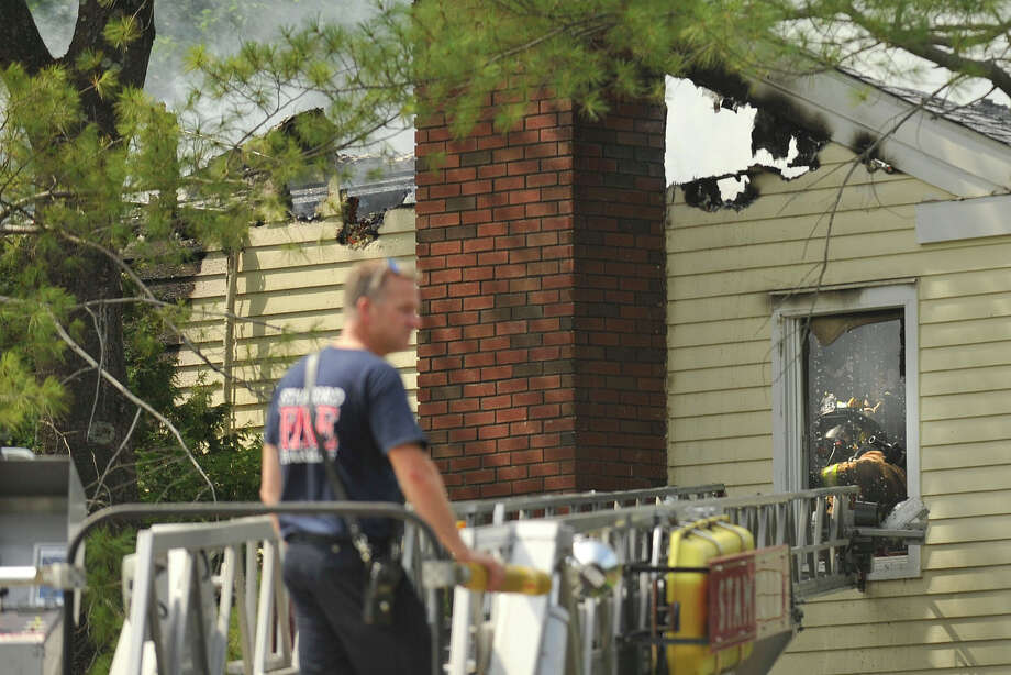 A Stamford firefighter can be seen through a window working at what is left from a fire that occured at 70 New England Drive in North Stamford, Conn., on Monday, Aug. 11, 2014. Photo: Jason Rearick / Stamford Advocate