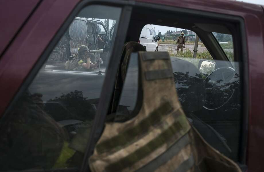 Ukrainian soldiers are seen through car windows taking up positions in the village of Mariinka. Photo: Evgeniy Maloletka, Associated Press