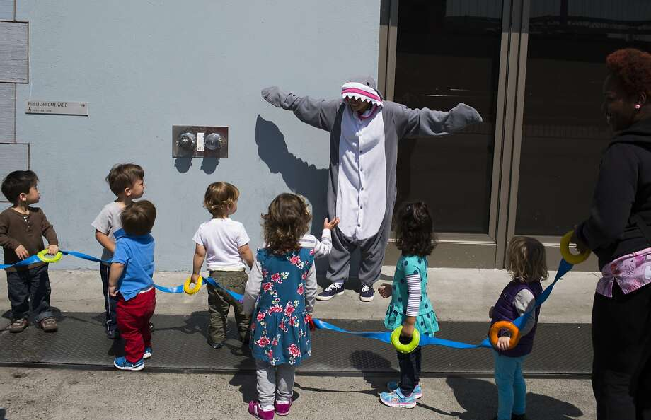 Rochelle Reuter, a Save the Bay intern dressed as the organization's shark mascot Spike, rode BART under the bay, appropriately, to Oakland on Monday to kick off Shark Week. Above, she waves to children outside the Ferry Building. Photo: Tim Hussin, Special To The Chronicle