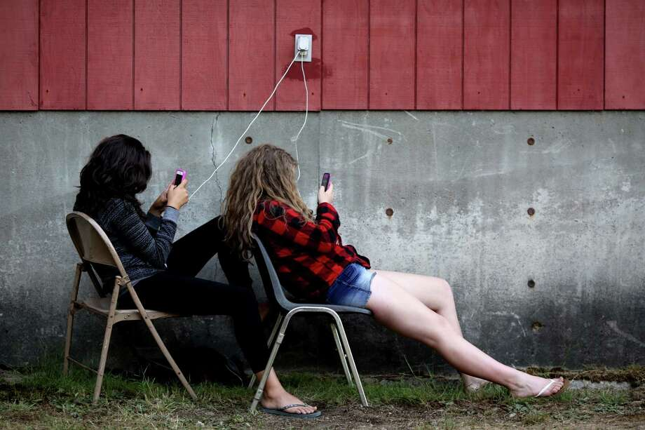 "Young women cluster near a bathroom electrical outlet, texting friends and family on the third and final day of the 14th annual Summer Meltdown, the ""Biggest Little Festival in The Northwest,"" on Sunday, August 10, 2014, at the Whitehorse Mountain Amphitheater in Darrington, Wash. Photo: JORDAN STEAD, SEATTLEPI.COM / SEATTLEPI.COM"