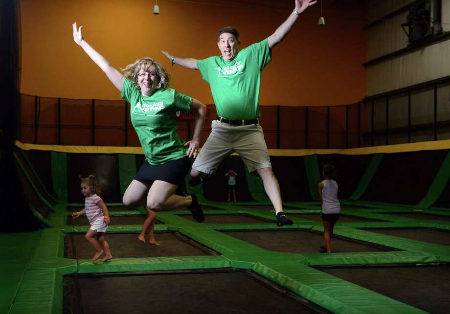 Owners Roni and Steve Rodier leap on the trampoline at ROCKINâÄô JUMP in Trumbull, Conn. Friday, Aug. 8, 2014. Photo: Autumn Driscoll / Connecticut Post