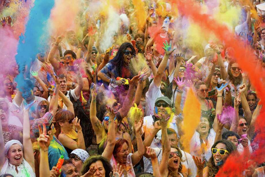 Revelers of the Holi Festival of Colors throw colored powders in the air in Madrid, Spain, Saturday, Aug. 9, 2014. The festival is fashioned after the Hindu spring festival Holi, which is mainly celebrated in the north and east areas of India. Photo: Daniel Ochoa De Olza, AP / AP