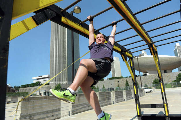 Patrick Dunham swings across the monkey bars set up on a parking garage rooftop during the Urban RAID race on Saturday, Aug. 9, 2014, in Albany, N.Y. The 5K obstacle course challenged runners with 13 obstacles, including a two-story-high cargo climb, Marine hurdles, ropes and the signature RAID-series wall. (Cindy Schultz / Times Union) Photo: Cindy Schultz, Albany Times Union / 00028102A