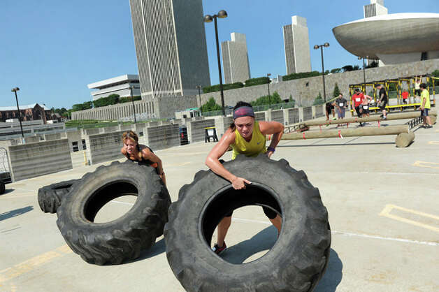 Dawn Valera-McGarry, left, and Molly Casey lift and push over tractor tires set up on a parking garage rooftop during the Urban RAID race on Saturday, Aug. 9, 2014, in Albany, N.Y. The 5K obstacle course challenged runners with 13 obstacles, including a two-story-high cargo climb, Marine hurdles, ropes and the signature RAID-series wall. (Cindy Schultz / Times Union) Photo: Cindy Schultz, Albany Times Union / 00028102A