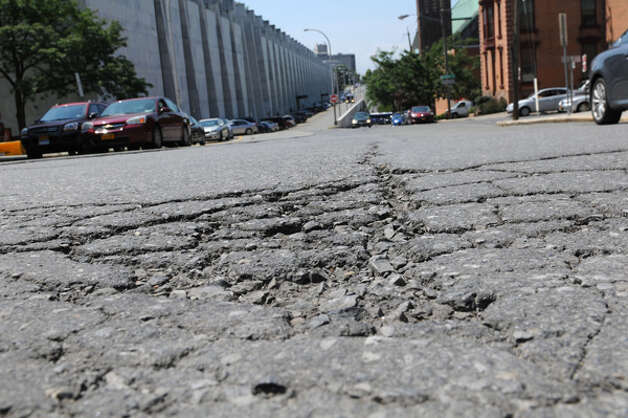 The pothole strewn road surface of South Swan St. on the Center Square side Monday, Aug. 11, 2014, in Albany, N.Y. (Will Waldron/Times Union) Photo: WW, Albany Times Union / 00028122A