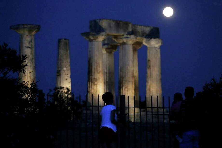 "People watch the super moon rising in the sky in front of the Apollo's temple at ancient Corinth about 80 kilometers (50 miles) southwest of Athens, on Sunday, Aug. 10, 2014. The phenomenon, which scientists call a ""perigee moon,"" occurs when the moon is near the horizon and appears larger and brighter than other full moons. (AP Photo/Petros Giannakouris) ORG XMIT: XPG102 Photo: Petros Giannakouris, AP / AP"
