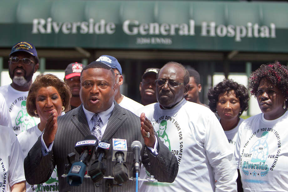 Supporters stand with Quanell X as he speaks in front of Riverside General Hospital, Wednesday, July 9, 2014, in Houston. The group is calling on the federal government to release the funds that are being held from the hospital because of the indictment of its former CEO Ernest Gibson. If the funds are not released the the city's first Negro hospital will close in six weeks and over 300 employees will lose their jobs. (Cody Duty / Houston Chronicle) Photo: Cody Duty, Staff / © 2014 Houston Chronicle