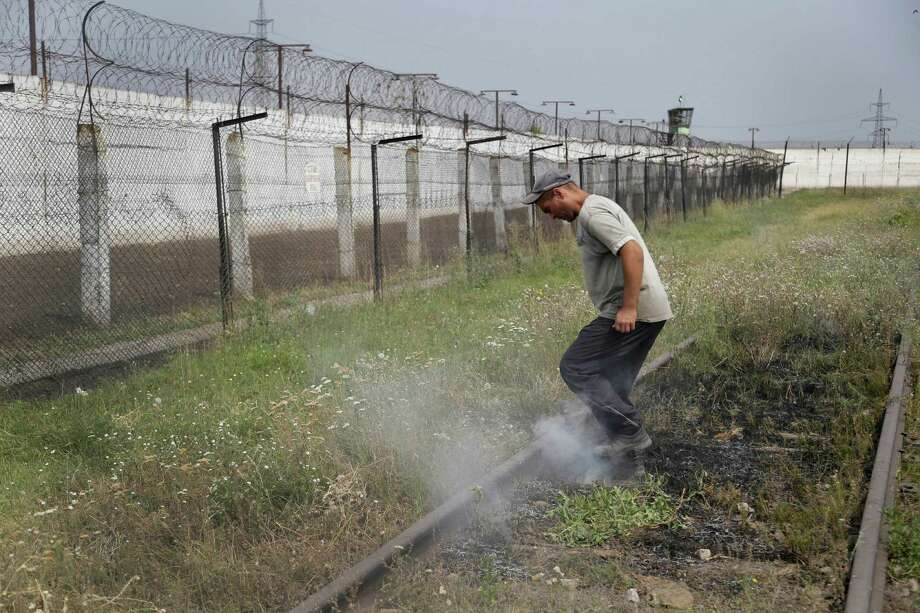 A prisoner tramples smoldering grass in a high-security facility after shelling in Donetsk, Ukraine on Monday. Local authorities say more than 100 prisoners have fled from a high-security facility after it was hit by shelling in Donetsk.  Photo: Sergei Grits, STF / AP