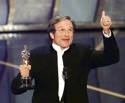 "Actor Robin Williams holds up his Oscar after winning in the Best Actor in a Supporting Role category during the 70th Academy Awards 23 March at the Shrine Auditorium in Los Angeles. Williams won for his role as a psychotherapist helping a troubled math genius in ""Good Will Hunting.""  Photo: Timothy A. Clary, AFP/Getty Images"