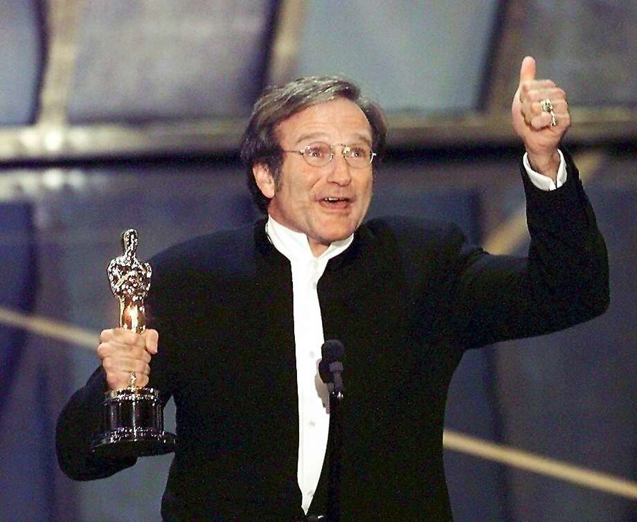 """Actor Robin Williams holds up his Oscar after winning in the Best Actor in a Supporting Role category during the 70th Academy Awards 23 March at the Shrine Auditorium in Los Angeles. Williams won for his role as a psychotherapist helping a troubled math genius in """"Good Will Hunting."""" Photo: Timothy A. Clary, AFP/Getty Images"""