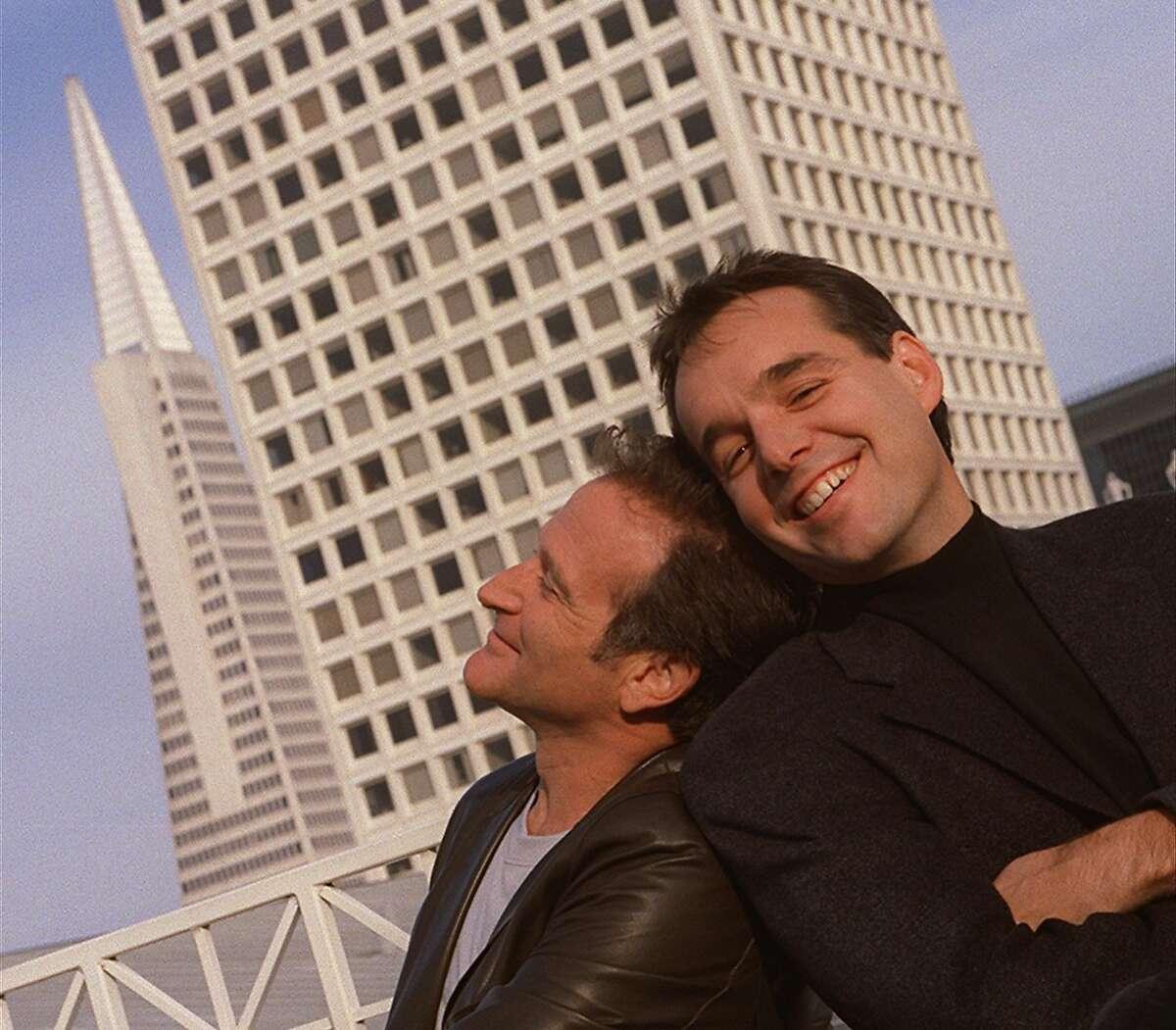 Robin Williams (left) and director Chris Columbus pose atop the Ritz-Carlton Hotel in San Francisco.