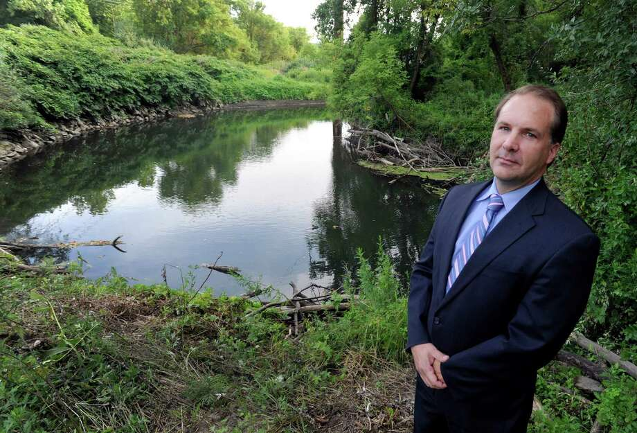 Attorney William Donaldson stands in front of an area of the Still River in Brookfield, Conn., that had previously been jammed up with debris and garbage, Monday, August 11, 2014. He along with several others, cleaned up the mess on Sunday. Photo: Carol Kaliff / The News-Times