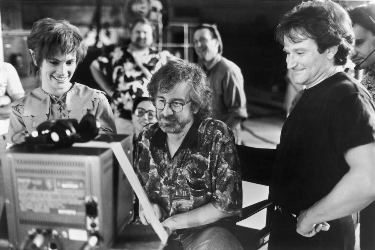 Actors Julia Roberts and Robin Williams watch daily production footage with director Steven Spielberg on the set of his film, 'Hook,' 1991.